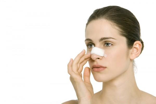 Nasenkorrektur: Frau mit verbundener Nase nach Nasen-OP