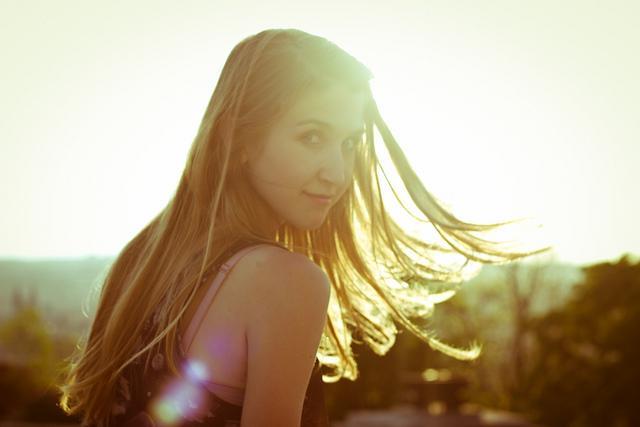 Hübsche Tschechin mit langen Haaren und Sonne im Hintergrund
