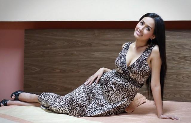 Schöne Vietnamesin mit langen schwarzen Haaren auf dem Bett liegend