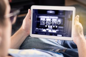 Man playing in an online casino with tablet. Modern gambling application. Slot machine app. Person holding smart mobile device in hand at home.