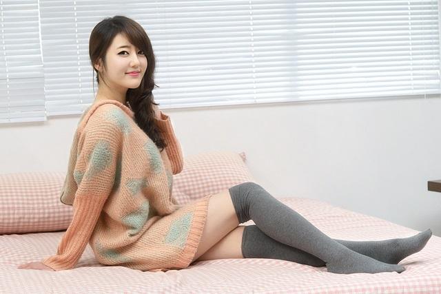 Süße Koreanerin auf dem Bett hockend